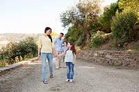Family walking down rural lane on holiday