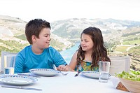 Brother and sister sitting at table on holiday