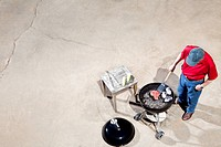 overhead view of a man bbq_ing a steak with sides