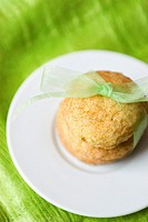 A small stack of cookies tied with a green ribbon on a white plate against a green background