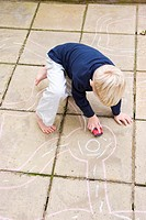 A young boy plays with his toy car on roads drawn on patio slabs with chalk