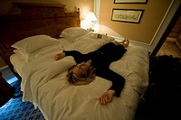 A woman relaxes on a hotel bed after a long day in Moscow, Russia.