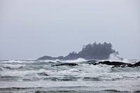 Waves crash into the beach on a stormy day.
