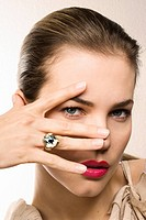 Young woman framing eye with fingers, close_up