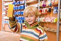 Child holding up a package of medicine