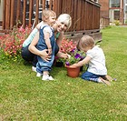 Smiling woman with two children in the garden plant flowers