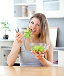 Bright woman eating salad in the kitchen at home