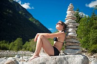 woman in bikini next to a stone pyramid, Valle Verzasca