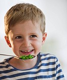 Young boy eating peas