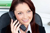 Positive young businesswoman talking on phone sitting in the office