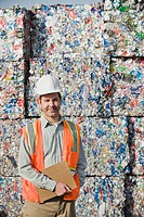 Worker standing in front of crushed aluminum cans