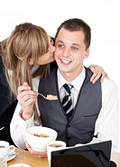 Beautiful blond businesswoman giving her smiling boyfriend a kiss at the breakfast table