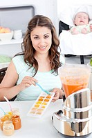 Caring mother preparing food for her lovely baby in the kitchen at home