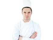 Attractive young chef with folded arms against white background