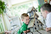Young boys looking at birdhouse