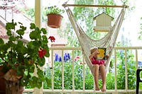 Young girl reading in hammock
