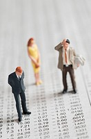 Figurines of people standing on stock chart