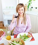 Bright young woman drinking wine and eating a salad in the kitchen at home