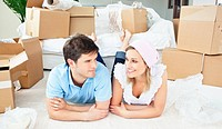 Young couple lying on the floor after unpacking boxes in their new house