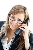 Assertive businesswoman talking on phone looking at the camera sitting in her office