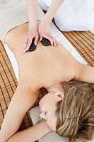 Pretty woman lying on a massage table having a stone therapy in a spa center