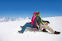 Smiling couple sitting on sled on snowy ski slope