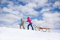 Couple walking up ski slope pulling sled
