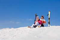 Couple sitting with skis in snow