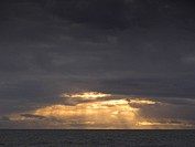 Storm clouds with sunbeams shining on tranquil ocean