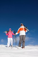 Skiers carrying skis and walking down ski slope