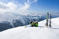 Couple laying in snow on mountain top with skis