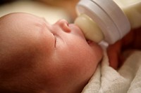 Baby girl drinking organic formula milk from a bottle  1 month old