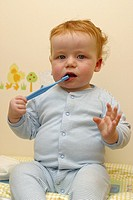 A baby brushing his teeth with a toothbrush