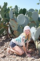 Blond model posing in front of opuntia