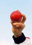 Close up of a young man holding a cricket ball