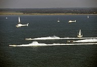 powerboat racers are shadowed by a helicoptor camera crew in ocean race