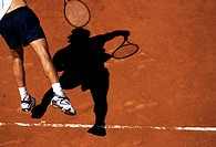 Tennis player serves on a red clay court