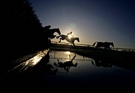 Steeplechase jockeys jump their horses over water jump