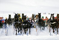 Group of ice jockeys racing by the side of a river in winter