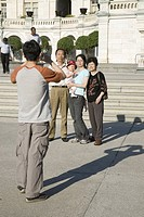 Asian man taking picture of Asian family standing in front of the U.S. Capitol, Washington, DC