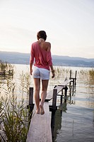 Young woman on a lakeside landing stage