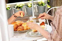 Two women eating a Hefezopf sweet bread from southern Germany for breakfast on the terrace