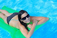 Attractive slim and tanned young lady lying on inflatable sunbed on sunny swimming pool on vacation or holiday