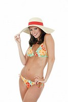Beautiful and sexy Caucasian waman in a flowered bikini wearing a hat