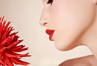 Close up of young beautiful woman inhaling red dahlia
