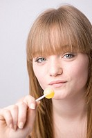 Close up of young woman eating lollipop and smiling