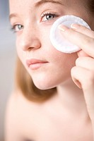 Close up of young woman removing make up with white cotton pad
