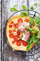 Pizza topped with tomatoes and Parma ham