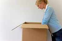 Young woman standing against white wall with her arms inside a cardboard box