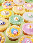 Lots of pastel_coloured fairy cakes decorated with sugar flowers